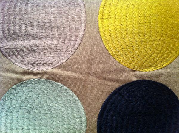 Detalle de motivos geométricos de color en un cojín