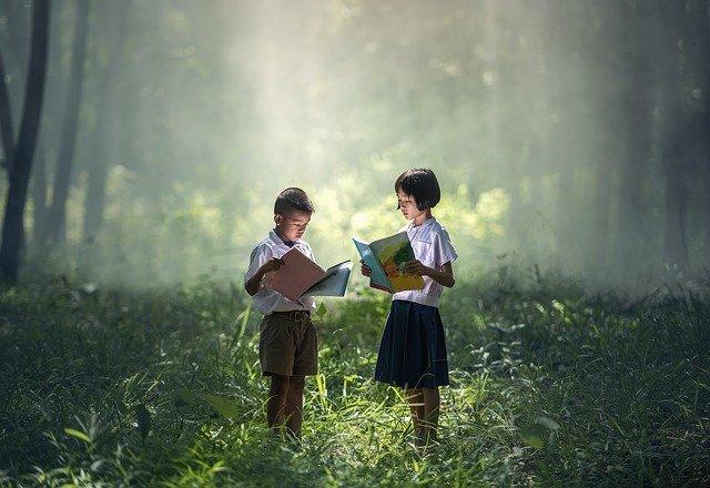 Dos niños leyendo en un bosque